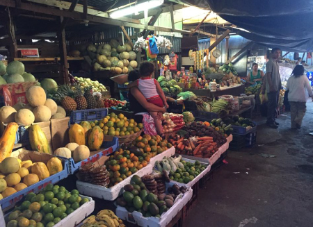 A fresh fruit and vegetable Market in Managua, with tarps overhead and a vendor holding a young child in her arms
